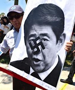 従軍慰安婦像の除幕式でナチス・ドイツのシンボルを重ねた安倍晋三首相の写真を掲げる参加者=30日、米カリフォルニア州グレンデール 【時事通信社】